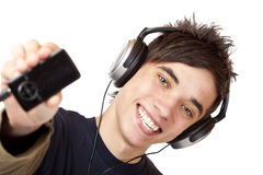 Teenager with headphones shows mp3 music player Royalty Free Stock Photo
