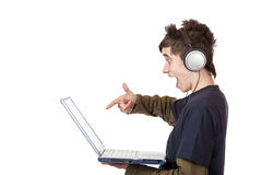 Teenager with headset points at computer Royalty Free Stock Images