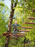 Teenager in helmet and with a safety rope boy goes on suspension bridge made of logs on the blurred background Stock Photos