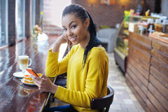 Teenager with her cell phone in bakery Stock Image
