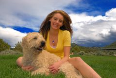 Teenager with her dog. On grass area Royalty Free Stock Image