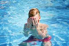 Teenager hides the face in hands in the pool. Concept of wound and trauma royalty free stock images