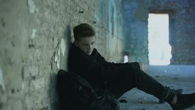 Teenager hiding from bullying in abandoned building, lonely, adolescent problems. Stock footage stock video