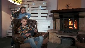 Teenager hiding the tablet screen from small sister. There is a fireplace in their living room at home stock video footage