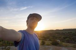 Teenager hipster traveler doing selfie overlooking on sunset. Wanderlust, Adventure, Vacation, concept.  stock photos