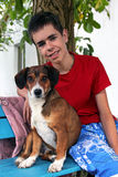 Teenager and his dog. Smiling teenager with his dog sitting on a bench and looking at the camera Royalty Free Stock Image