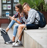 Teenager and his girlfriend with smartphones Stock Image