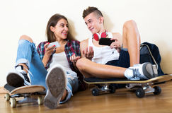 Teenager and his girlfriend with smartphones. At home Stock Photos