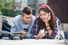 Teenager and his girlfriend with smartphones Royalty Free Stock Images