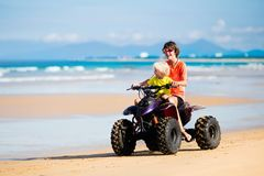 Kids on quad bike. Off road all terrain vehicle. Teenager and his little brother riding quad bike on tropical beach. Active teen age boy on quadricycle. All Stock Photo