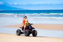 Kids on quad bike. Off road all terrain vehicle. Teenager and his little brother riding quad bike on tropical beach. Active teen age boy on quadricycle. All Royalty Free Stock Photography