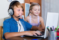 Teenager and his little sister playing game. On laptop royalty free stock image