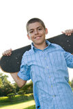 Teenager with His Skateboard. A boy in his early teens happily posing with his skateboard Stock Photo