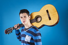 Teenager holding a classic guitar. With blue background Royalty Free Stock Image
