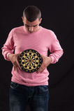 Teenager holding a dartboard with his hands Royalty Free Stock Image