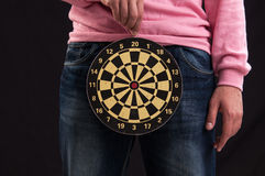 Teenager holding a dartboard with his hands Royalty Free Stock Images