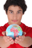 Teenager holding a mini-globe Stock Photo