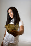 Teenager holding money (american dollars). A young girl holding paper money. Hispanic/Latin, happy.  Can denote babysitting and odd jobs, success, materialism Stock Photo