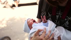 Teenager holding a newborn baby boy in her arms. Wiggle it. Cares stock video