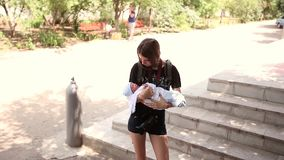Teenager holding a newborn baby boy in her arms. Wiggle it. Cares. stock video