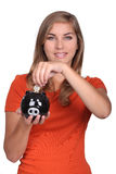 Teenager holding piggy bank. Teenager placing coins in a piggy bank Royalty Free Stock Image