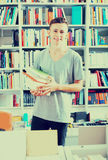Teenager holding pile of books. Smiling teenager holding pile of books in hands in store Stock Photos
