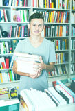 Teenager holding pile of books. Smiling young boy teenager holding pile of books in hands in store Stock Images