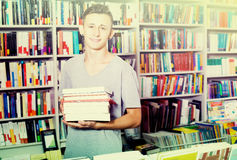 Teenager holding pile of books. Smiling young teenager holding pile of books in hands in store Royalty Free Stock Photos