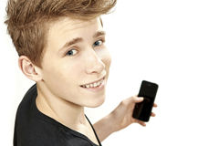 Teenager holding smartphone and smiles Royalty Free Stock Image