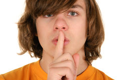 Teenager holds finger before lips Royalty Free Stock Image