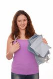Teenager holds scissors and pieces of jeans. Royalty Free Stock Images