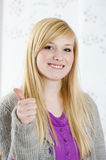 Teenager holds up thumb. At home stock photography
