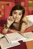 Teenager with homework. Close up of teenager lying on bed with homework books Stock Images