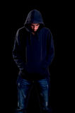 Teenager with hoodie looking down over black background Stock Images