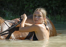 Teenager and horse in river stock images