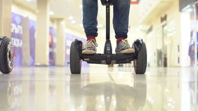 Teenager on hyroscooter in a modern shopping center. Close up of man`s legs on two wheels electric gyro scooter. Teenager on hyroscooter in a modern shopping Royalty Free Stock Photo