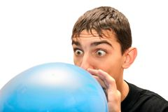 Teenager inflating a balloon. Teenager inflating big blue balloon. Isolated Royalty Free Stock Image