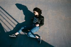 Pretty girl with curly hair resting in skateboard park. Portrait of beautiful young girl in the skate park. Young girl with curly Royalty Free Stock Images