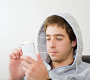 Teenager and iphone. Teenager using his iphone mobile phone Stock Photos