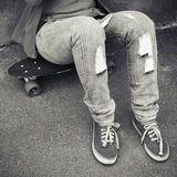 Teenager in jeans and gumshoes sits on skateboard Stock Photos