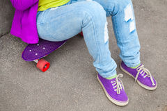 Teenager in jeans and gumshoes sits on a skateboard Stock Image