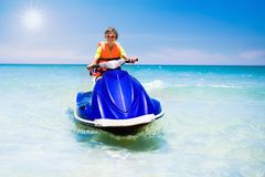 Teenager on jet ski. Teen age boy water skiing. Teenager on jet ski. Teen age boy skiing on water scooter. Young man on personal watercraft in tropical sea Royalty Free Stock Photography