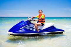 Teenager on jet ski. Teen age boy water skiing. Teenager on jet ski. Teen age boy skiing on water scooter. Young man on personal watercraft in tropical sea Royalty Free Stock Image