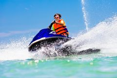 Teenager on jet ski. Teen age boy water skiing. Teenager on jet ski. Teen age boy skiing on water scooter. Young man on personal watercraft in tropical sea Stock Photography