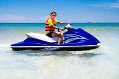 Teenager on jet ski. Teen age boy water skiing. Teenager on jet ski. Teen age boy skiing on water scooter. Young man on personal watercraft in tropical sea royalty free stock images