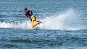 Teenager on Jet Ski-Water Sports in the summer having fun on the beach royalty free stock photos
