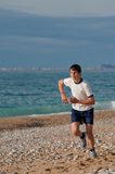 Teenager jogging. Early morning on a beach Royalty Free Stock Image