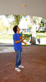Teenager juggler. A young boy juggling in a open scenario plays with five yellow balls Stock Image
