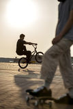 Teenager jump on bicycle outdoors, boy on skateboard, urban styl stock images