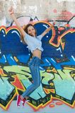 Happy teenager jumping. A teenager is jumping against a graffiti wall after a day at school Stock Images
